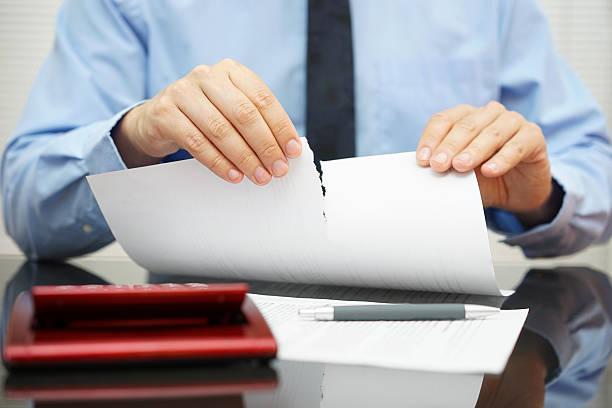 businessman+tears+document+in+office