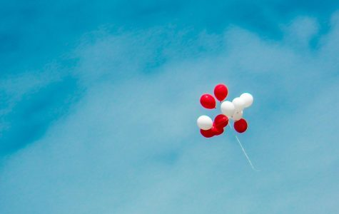 Image of red and white balloons drifting into the air